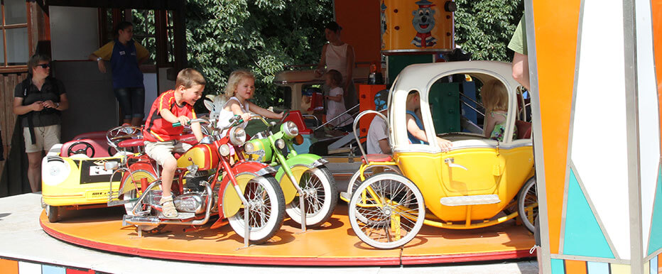 Kies je favoriete voertuig op deze carrousel! Stap in een oldtimer, een koets en beleef een dolle rit!